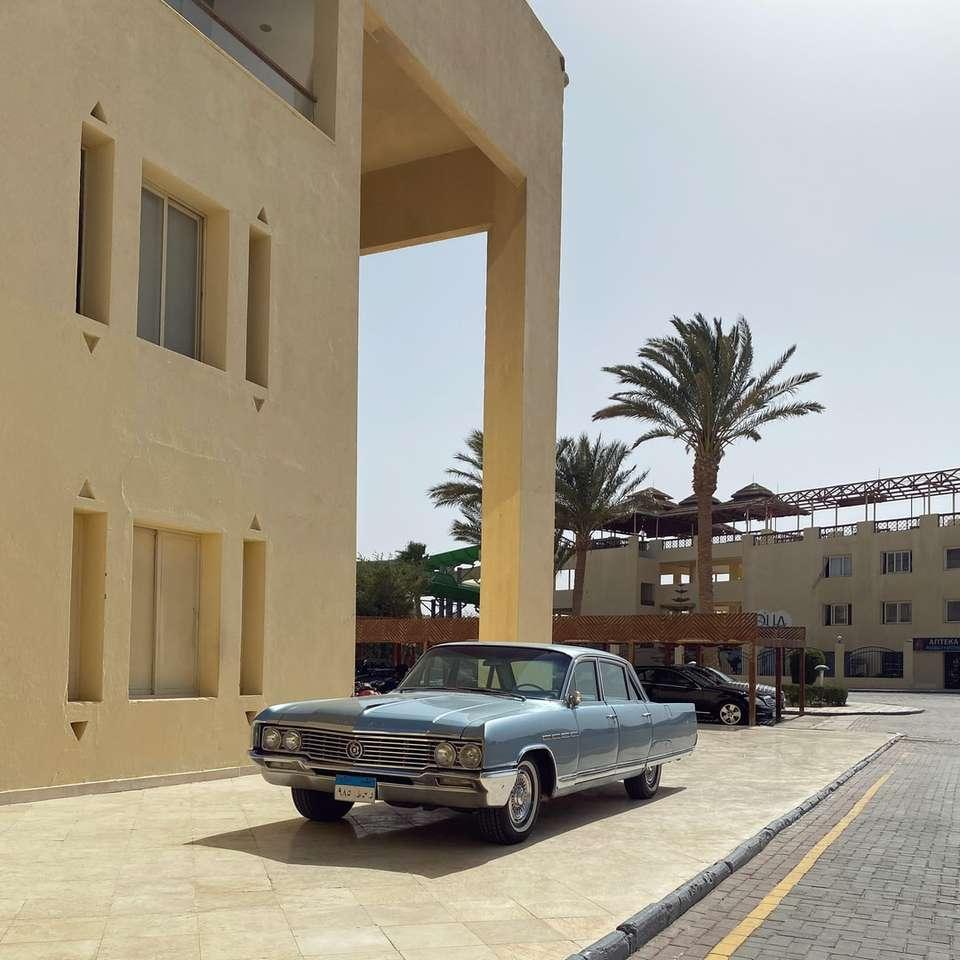 Zwarte sedan geparkeerd naast het betonnen bouwen van beige puzzel