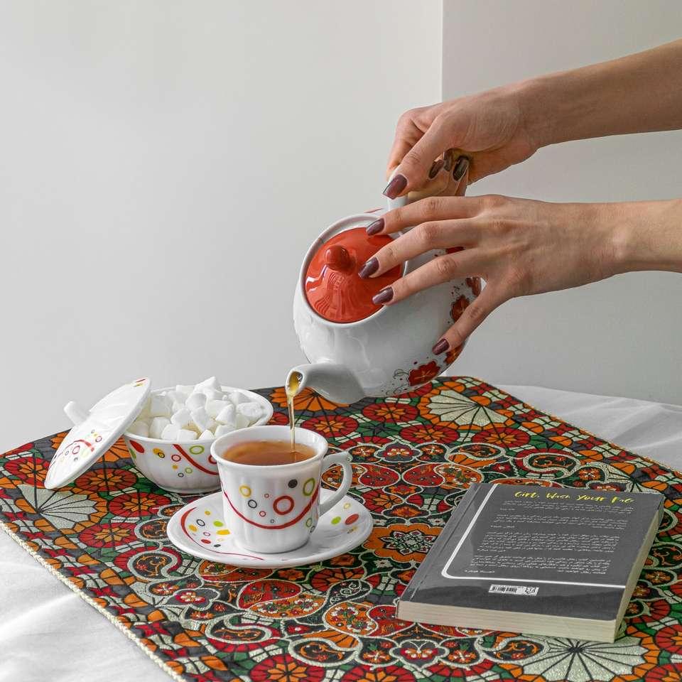 Personne tenant une tasse en céramique rouge