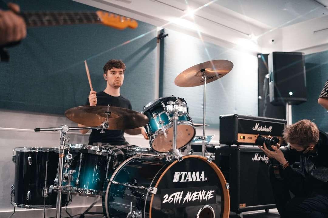 Mann im schwarzen Hemd, das Drum-Set spielt