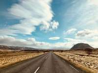 Сив асфалтов път под синьо небе и бели облаци