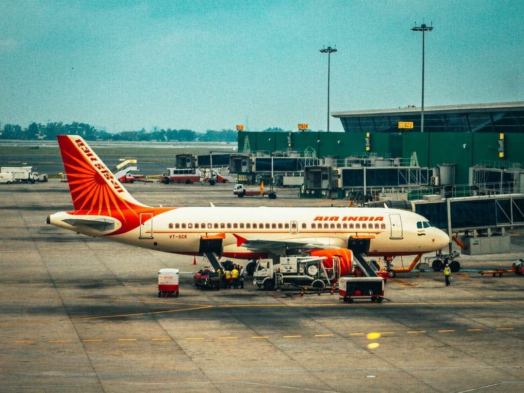 bílé a červené letadlo na letišti během dne