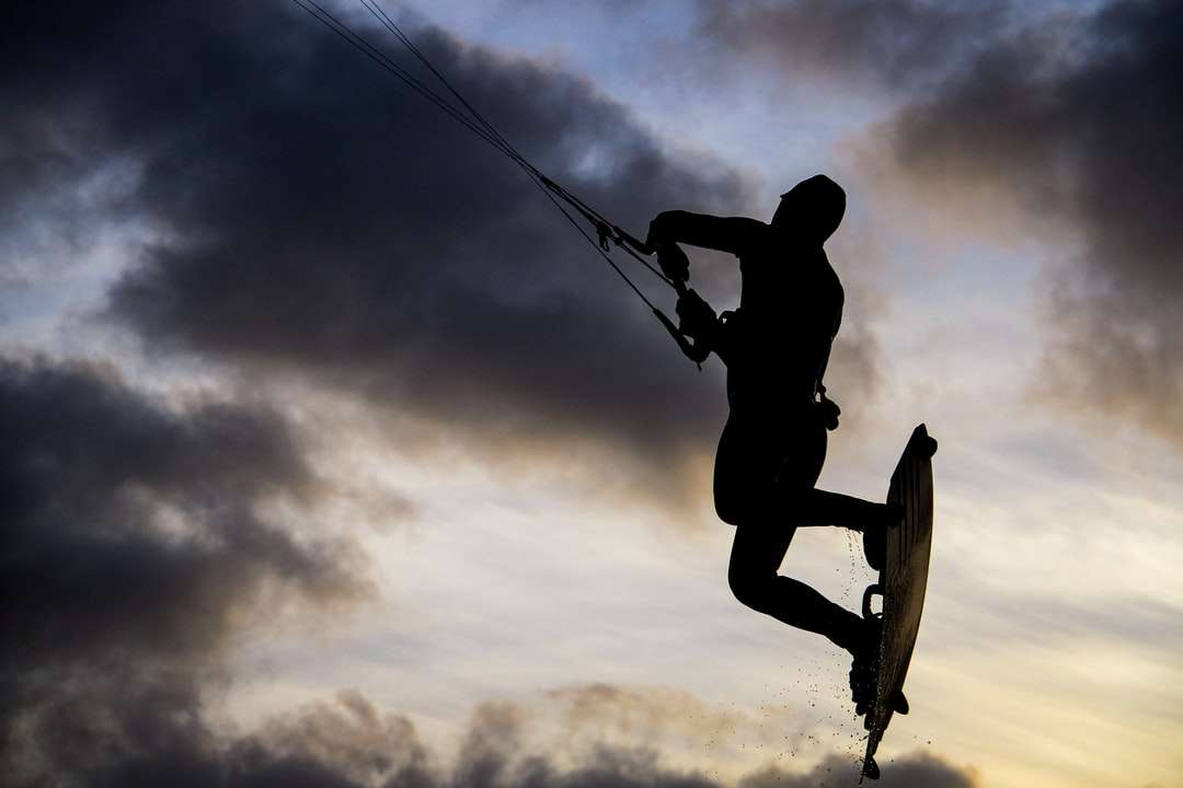 Silueta člověka na skateboard pod zatažené obloze