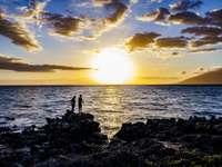 Silhouette de personne debout sur le rocher près du corps d'eau