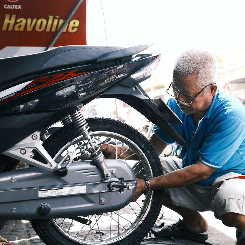 Muž v modré košile s dlouhým rukávem sedí na černém motocyklu online puzzle