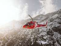 red and white helicopter flying over snow covered mountain