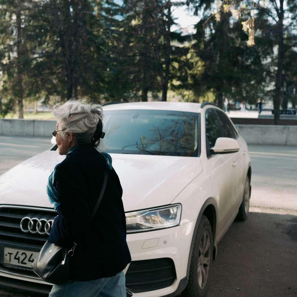 Kobieta w czarnej kurtki stoi obok białego audi samochodu puzzle