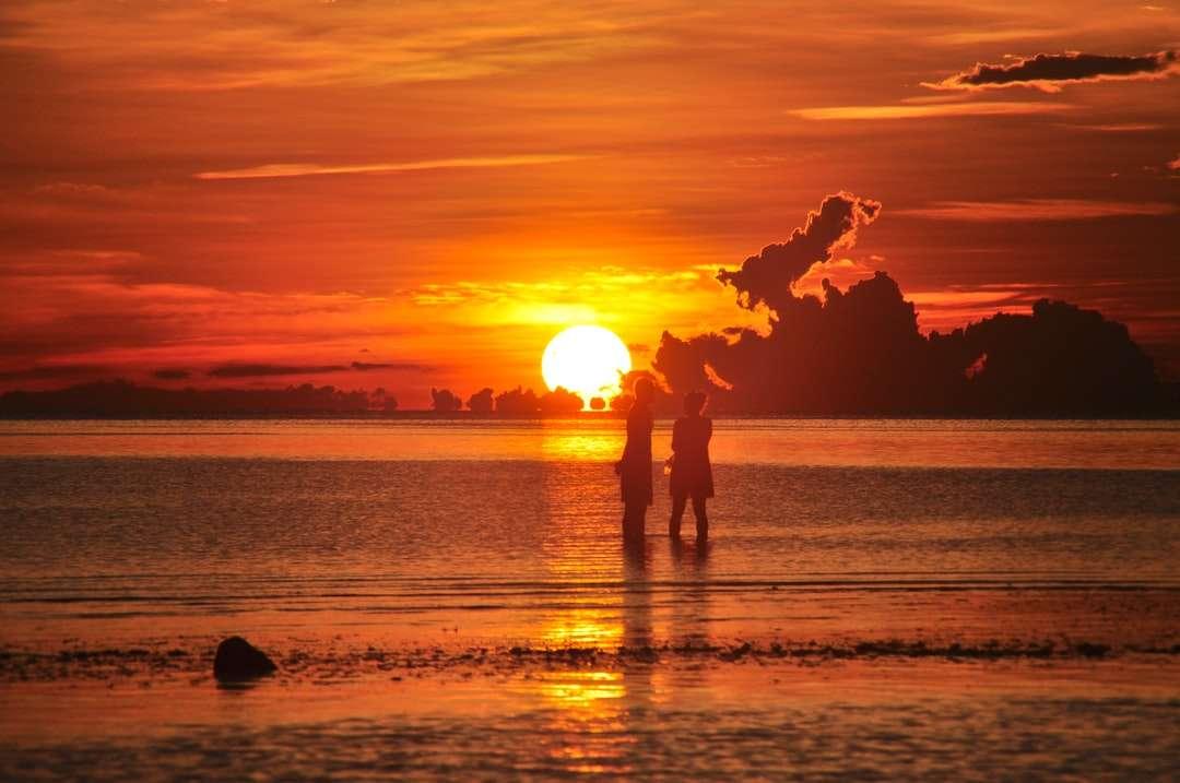 Silueta 2 lidé stojící na pláži při západu slunce skládačka