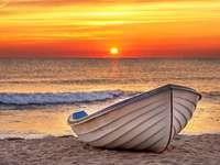 Αλιευτικό σκάφος στην παραλία κατά την ανατολή του ηλίου