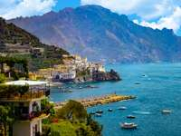 The view of Amalfi coast. This is on the south of Italy in Europe. The city stands on cliffs above the sea. There are boats on the sea. online puzzle