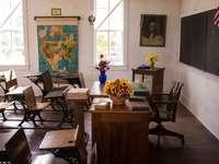 Ledigt vitt målat klassrum med stolar, bord