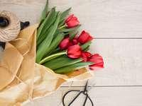 Röd tulpanblommor bukett på brun träpall