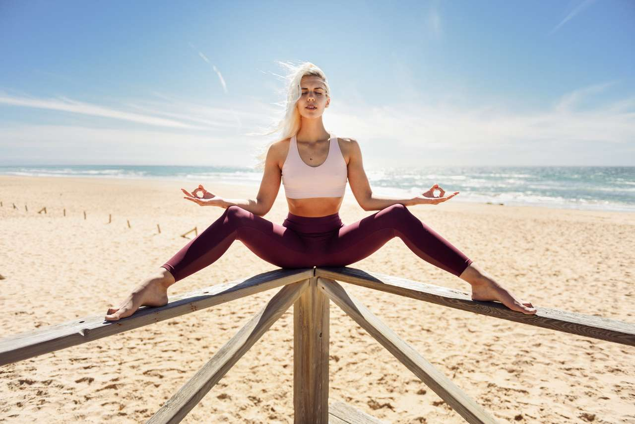 Caucasian blonde woman practicing yoga in the beach puzzle