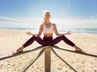 Donna bionda caucasica che pratica yoga in spiaggia