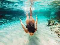 woman in black bikini swimming in the water