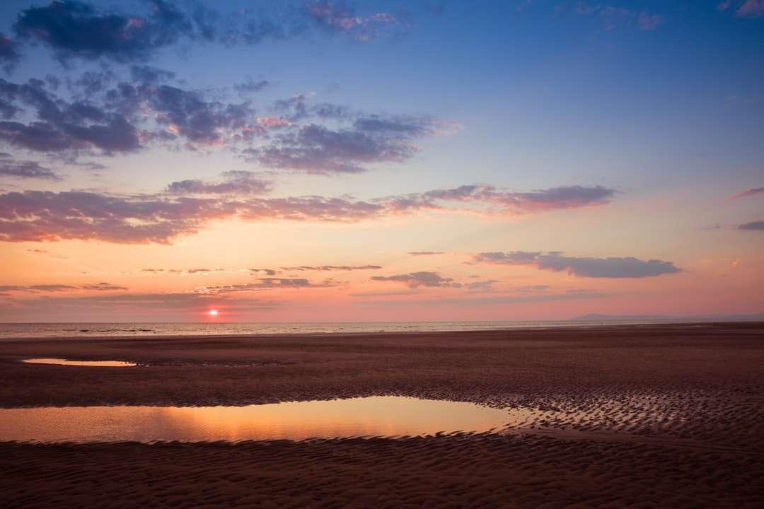 mořské vlny narážející na břeh při západu slunce skládačka